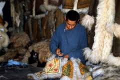 An Afghan artisan stitches sheepskin jackets in this coat shop, 1974. ©Peter Loud   peterloud.co.uk