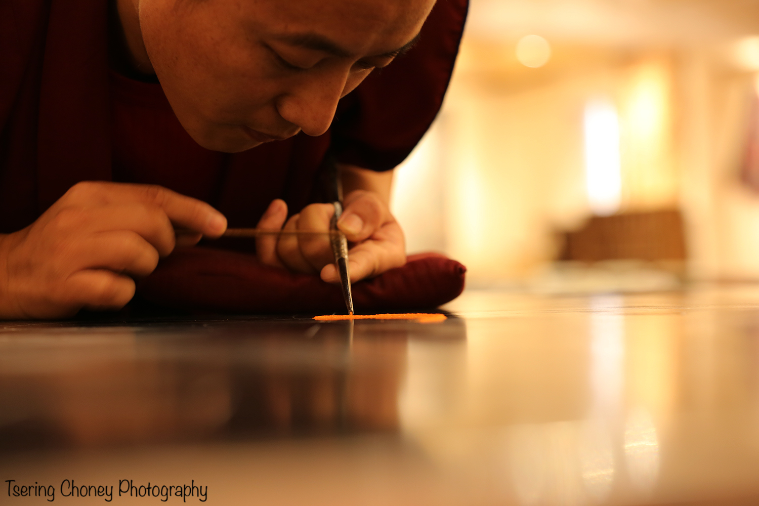 A monk from the Drepung Losling Monastery pours sand to create a Sand Mandala at Seret & Sons Gallery.