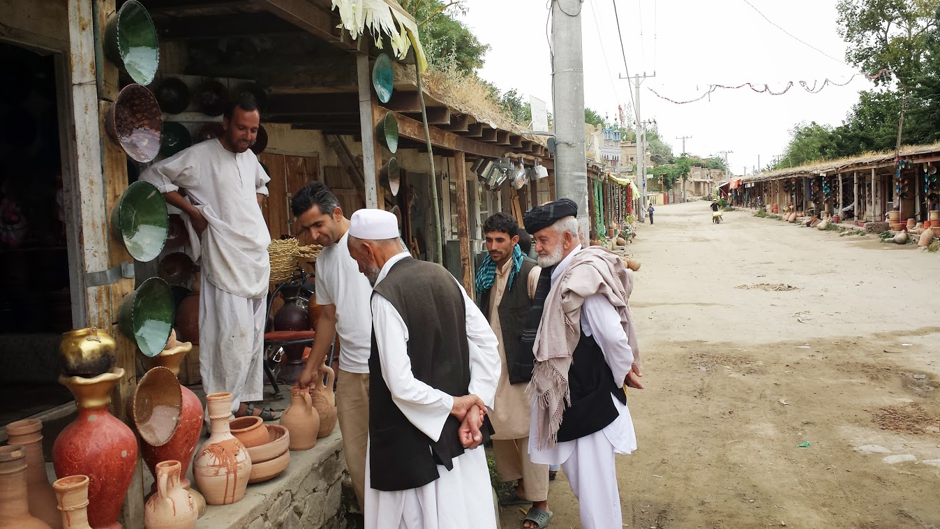 Abdul Istalifi discussing pottery with local merchants in Istalif, Afghanistan.