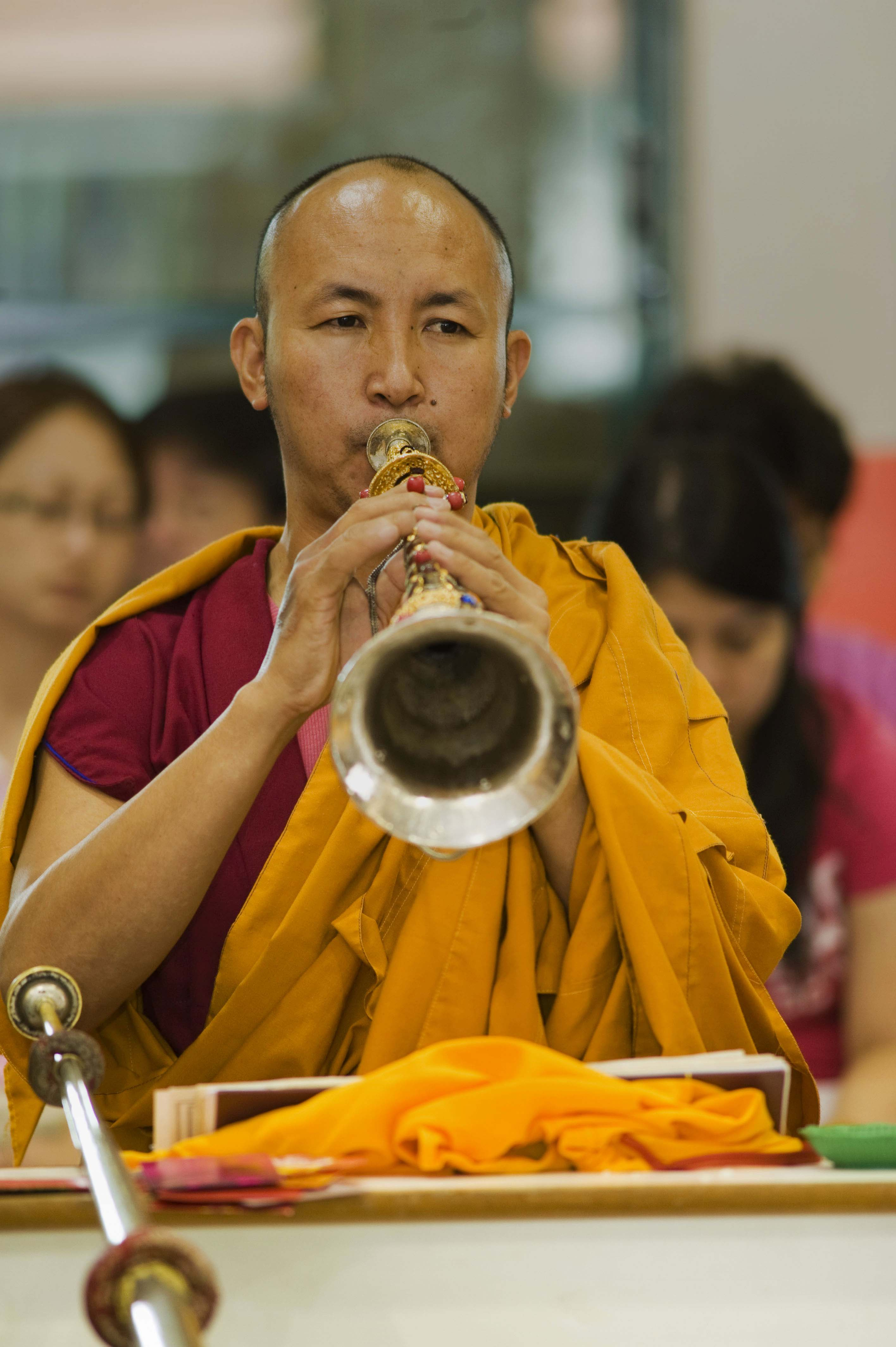 A Tibetan Monk practices playing the horn.